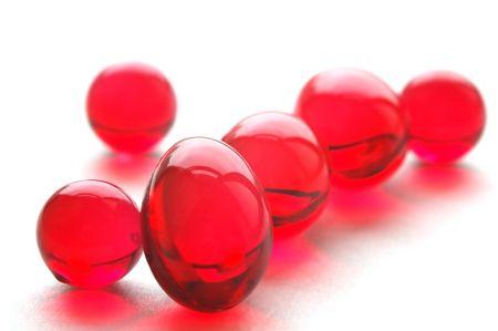 Close up of vitamins E pills, red capsules Stock Photo