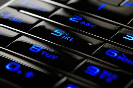 Close up shot of blue mobile keypad under dark environment