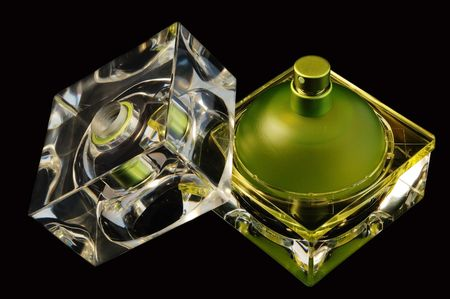 An open perfume bottle over black background photo