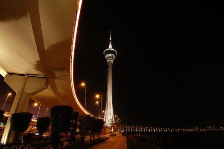 Night scene of Macau Tower Convention under a bridge