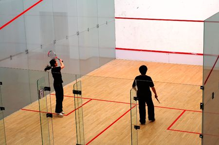A couple of young boy and girl playing squash
