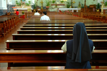 christian altar: A back view of praying sister inside church