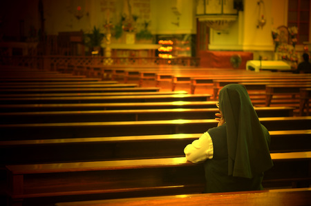 A back view of praying sister inside church
