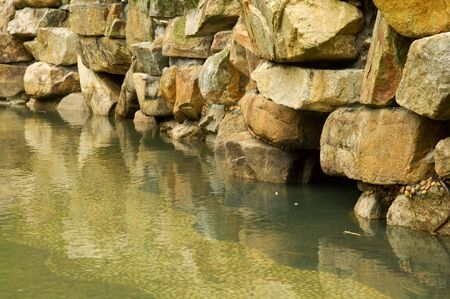 back yard pond: The stone wall of back yard pond Stock Photo