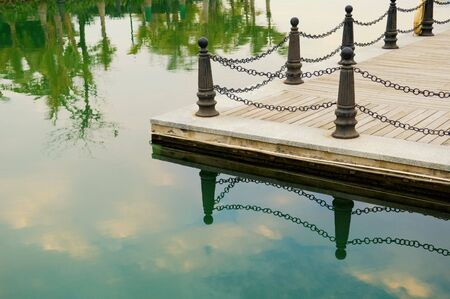 bollards: Railing posts of lake shore and its reflection over water