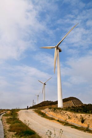 White electrical power generating wind turbines on rolling hills Stock Photo - 5411536