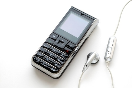 A modern mobile phone and the wired head-phone Stock Photo - 9956709