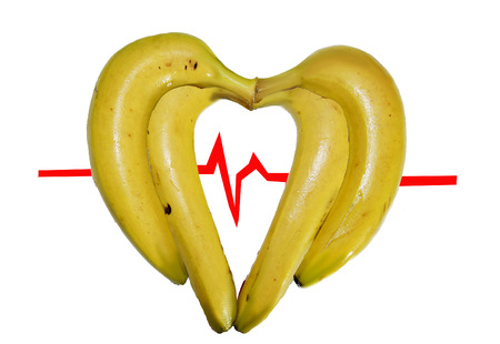 studio photograph: studio photograph with health theme, which can see a heart formed by yellow bananas with an electro cardiogram background.