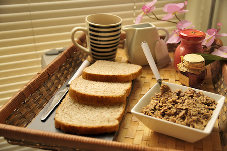 studio photograph: Thematic studio photograph of healthy feeding, which can be balanced breakfast tray with cup of coffee, milk, sliced bread, jam, fresh tomato and tazn cereal. Stock Photo