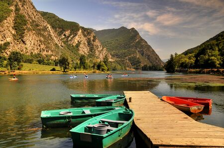 rowboats: jetty on mountain lake with kayaks and rowboats in the mountain