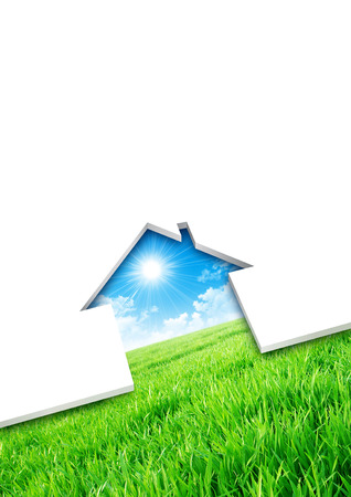 building material: Eco house concept. Cutting of a blank sheet, house shaped above a green field background