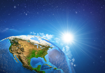 Rising sun over the Earth and its landforms, view of the United States of America. Elements of this image furnished by