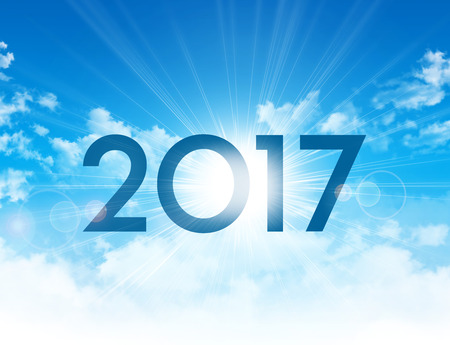 New Year 2017 type high in blue sky with the sun rising up behind 스톡 콘텐츠