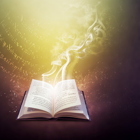 Open old book on the magic code of a spell, mysterious smoke and mystic bright light Фото со стока