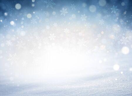 Fiocchi di neve e nevicate su uno sfondo invernale blu freddo e un terreno di neve polverosa. Materiale stagionale invernale.