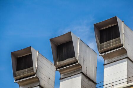 3 Air Exhaust Vents in a row on a building rooftop 写真素材