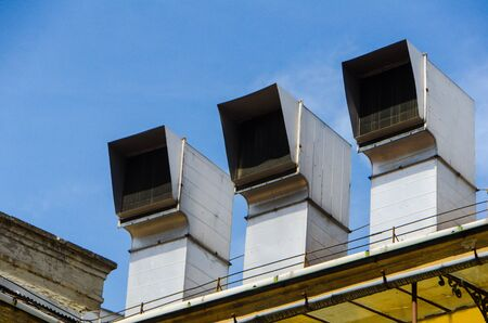 3 Air Ducts in a row on a building rooftop 写真素材