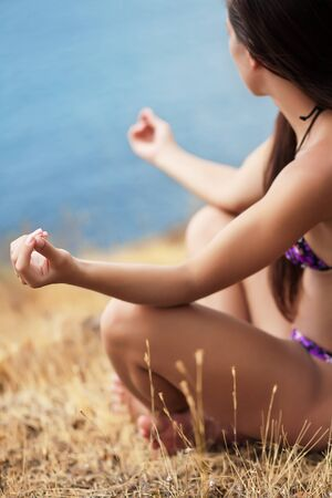 beautiful girl in a meditation on the beach photo