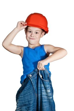 arrogancia: niño con casco y en pantalones vaqueros demasiado grandes Foto de archivo