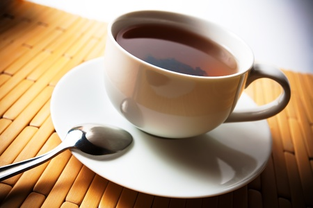 cup of tea in a white cup on a bamboo background photo
