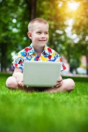 Netter kleiner Junge sitzt mit einem Laptop auf der Wiese