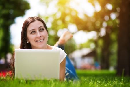 Happy lachende meisje tot op het groene gras met laptop