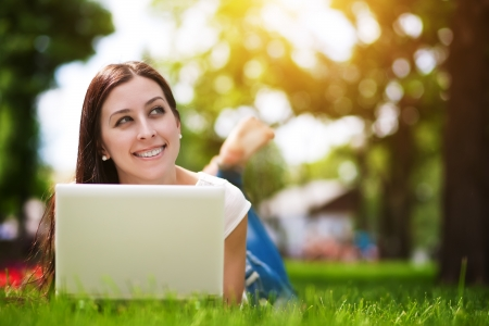 Happy smiling girl laying on the green grass with laptop Stock Photo