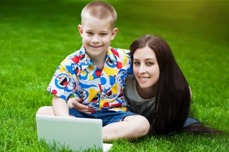 smiling Mother and son  in the green grass with laptop photo