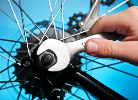 repair of a bicycle with a wrench Stock Photo