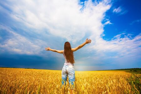 arms  outstretched: Girl with outstretched arms is enjoys summer day in the field Stock Photo