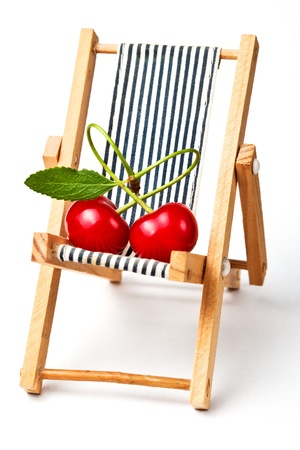 couple in love  heart with red cherryes on the beach chair isolated on the white photo