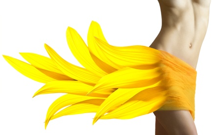 Mooie vrouw met zonnebloem gele bloemblaadjes op haar heupen