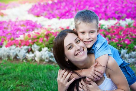 smiling Mother and son  in the green grass photo