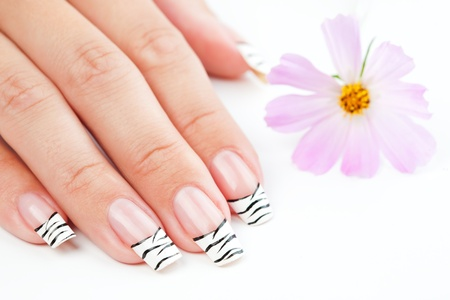 Hands with striped french manicure  relaxing with flowers