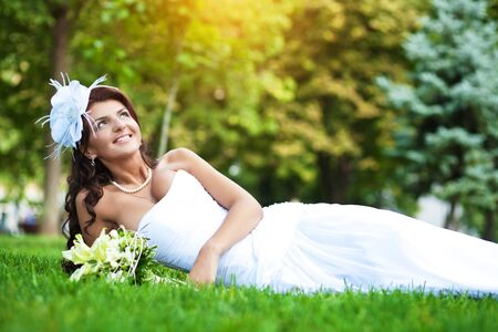 beautiful bride in white dress lying on green grass photo