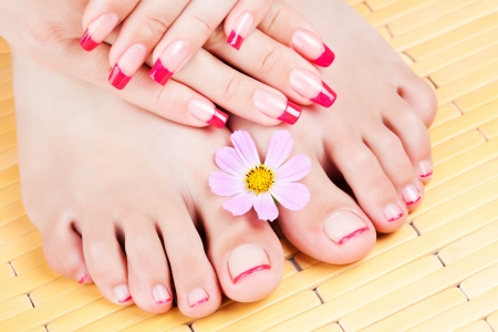 feet relaxing: Woman hands and feet with pink manicure, pink flower Stock Photo