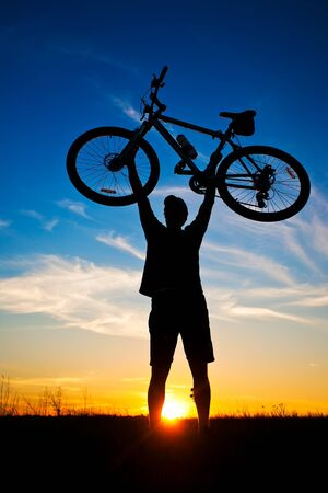 cyclist with a bike silhouette on a blue sky Stock Photo - 15399101