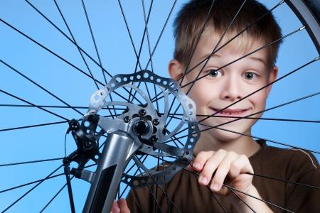 Boy is repairing the bicycle wheel