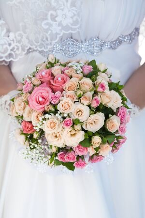 bouquet of pink roses in the bride s hands photo