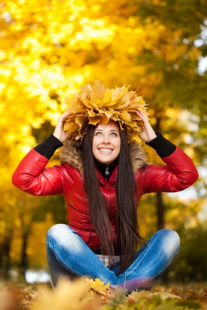 cheerful girl in a wreath on a autumn leafs background photo