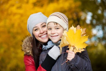 happy Mom and son on a yellow autumn park background Stock Photo - 15895133