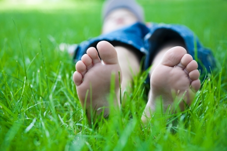 Children s feet on grass  picnic in spring park