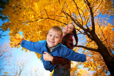 happy mother and son are playing in the autumn park Stock Photo - 15976574