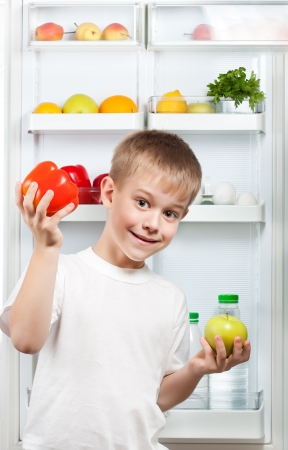 happy boy near the open refrigerator Stock Photo