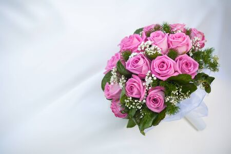 bouquet of pink roses on the white wedding dress photo