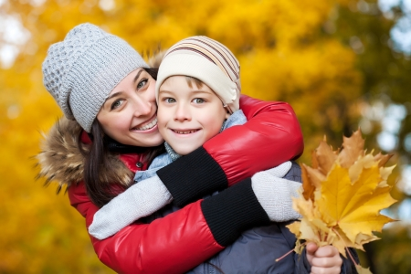 happy Mom and son are playing in a yellow autumn Stock Photo - 16953016