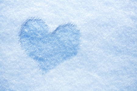Heart from ice on snow background photo