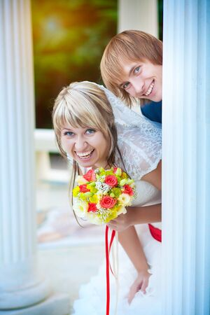 happy newlyweds near white column Stock Photo - 16977232