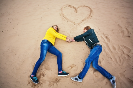 couple are lying on the sand with a heart Stock Photo - 17135530