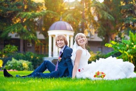 happy couple are sitting on the green grass photo